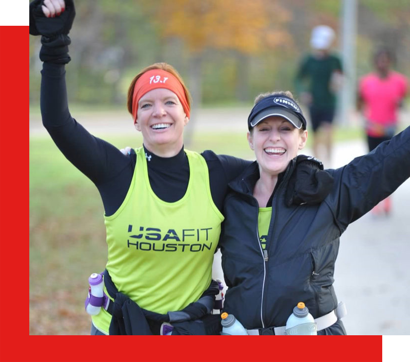 two smiling runners wearing USA Fit Houston shirts waving to camera